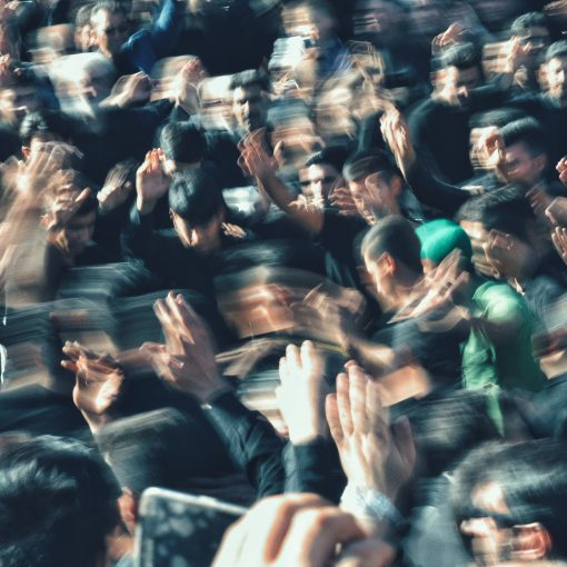 Zu sehen sind viele Leute, die ihre Hände hochhalten. Das Bild ist verwischt und deutet auf eine hohes Audience Engagement hin.