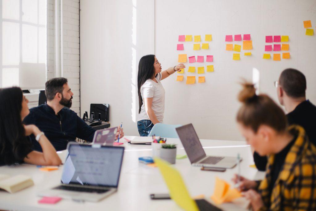 Mehrere Leute sitzen zusammen an einem großen Tisch und planen gemeinsam ihre nächste Innovation.
