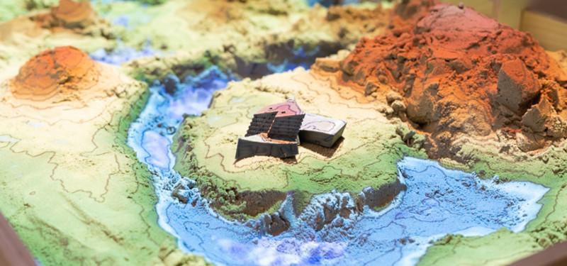 In der Sandbox werden zum Beispiel virtuelle Darstellung und haptisches Erleben zusammen gedacht. In der Mitte der AR-Projektion befindet sich ein 3D-Modell des Zentralgebäudes (c) FabLab Lüneburg.